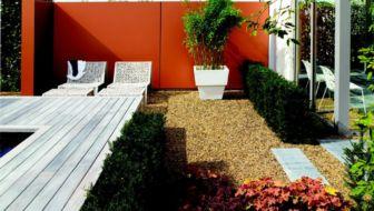 tuintrend - oranje muur met bamboe in bloembak en een zitje